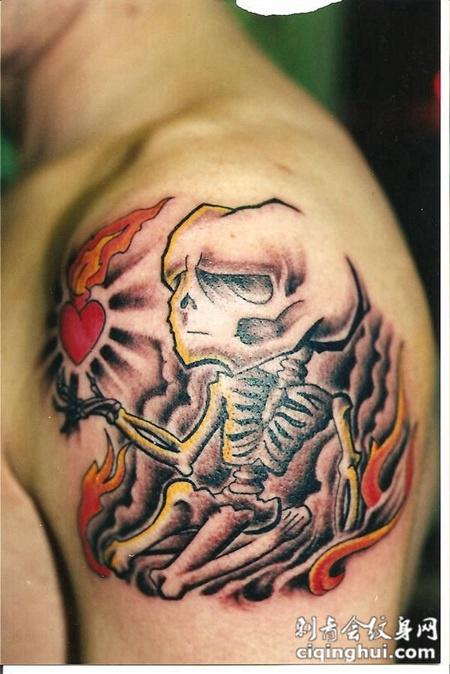 大臂上托着心的骷髅纹身图案