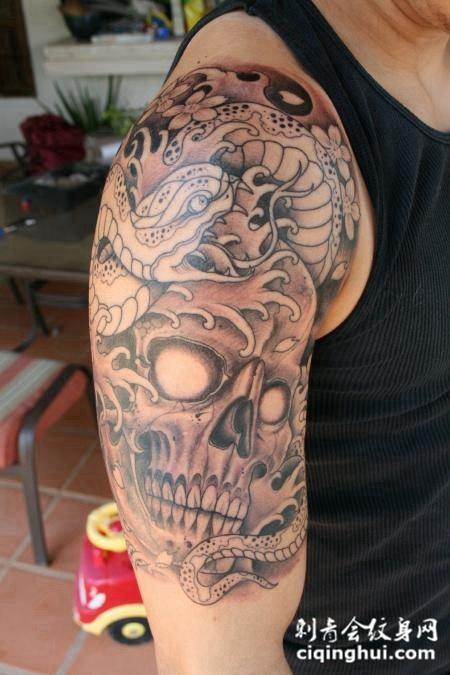大臂上的骷髅头蛇纹身图案