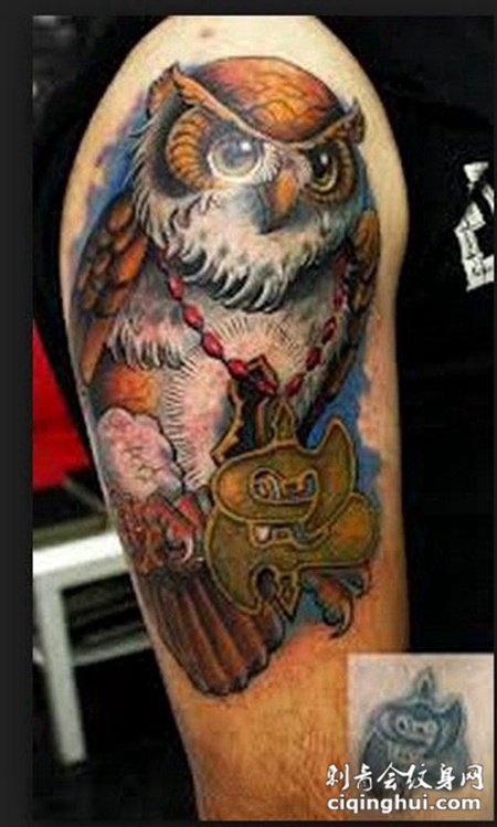 大臂上挂着牌子的猫头鹰纹身图案