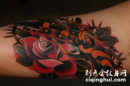 大臂上的玫瑰花手枪纹身图案