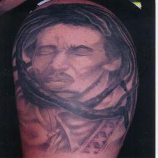 大臂上的被树枝缠绕的男子纹身图案