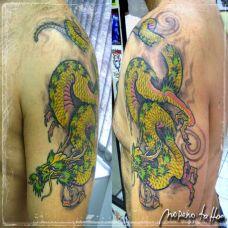 大臂上的一条绿色的龙纹身图案
