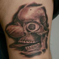 大臂上的雕刻娃娃纹身图案