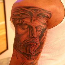 大臂上的雕刻耶稣纹身图案