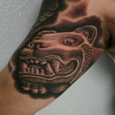 大臂上的雕刻狮子纹身图案