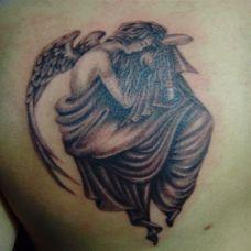 后背上蜷缩着的天使纹身图案