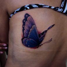 后背上的紫色蝴蝶纹身图案