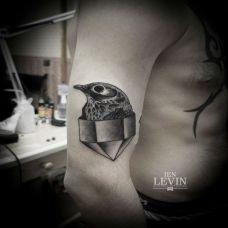 大臂上几何体中的小鸟纹身图案
