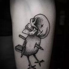 小臂上的骷髅鸟纹身图案