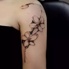 大臂上的黑灰色桃花纹身图案