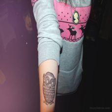 小臂上的黑色猫头鹰纹身图案