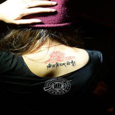 女生背部艺术莲花与藏文纹身图案