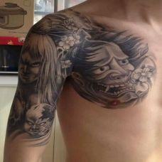 男子肩部黑色半甲般若纹身图案