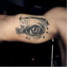 男人胳膊上黑色眼球刺青图案