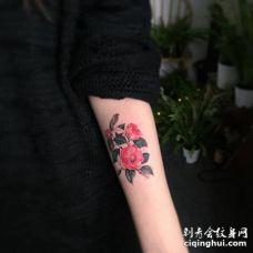手臂漂亮的逼真茶花花朵与枝叶纹身图案