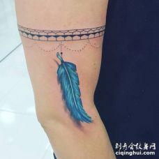 牙齿形状的臂环和蓝色羽毛纹身图案