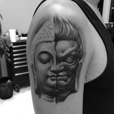 大臂上简约的佛魔图案个性纹身
