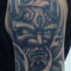 大臂上的鬼头纹身图案