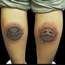 双腿上哭脸笑脸石裂纹身图案