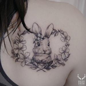 女生肩部小白兔纹身,一只躲在花环里的小白兔