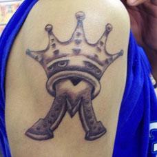 大臂上戴着皇冠的字母纹身图案