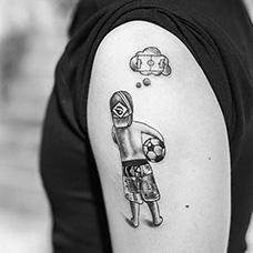 大臂抱着足球的男孩纹身图案